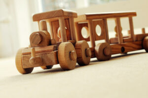 Mamljiva lesena igrače vlakec, ki ponuja razvoj motorike.