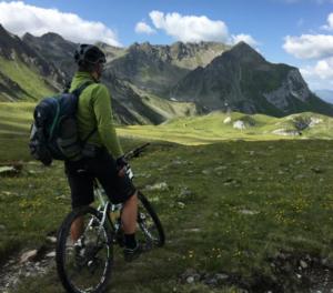 Rekreativni kolesar v zeleni majici in kratkih črnih hlačah v prelepi naravi med gorami.