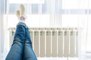 Noge naslonjene na beli radiator pod oknom.